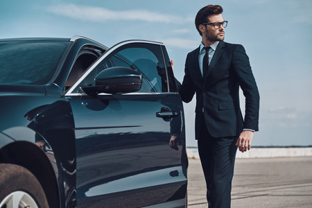 Getting ready to drive. Handsome young businessman entering his car while standing outdoors