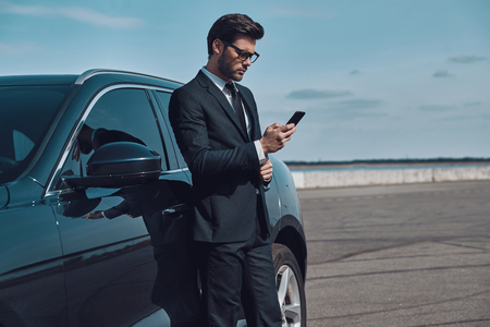 Portrait of confidence. Handsome young businessman using smart phone while standing near his car outdoors