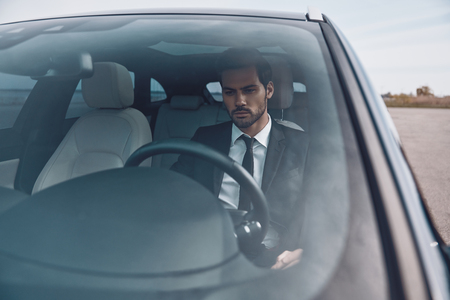 Hurrying to get things done. Handsome young man in full suit looking straight while driving a car 免版税图像