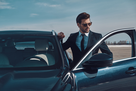 Luxury style. Handsome young businessman entering his car while standing outdoors Banco de Imagens - 122384162