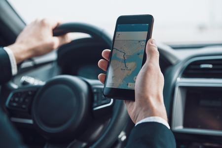 最短の方法を探しています。車を運転しながら地図をチェックするためにスマートフォンを使用して若い男のクローズアップ 写真素材
