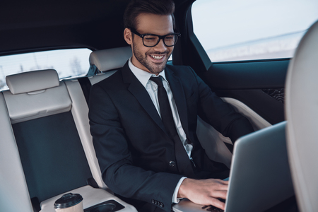 Planning new business strategy. Handsome young man in full suit working using laptop and smiling while sitting in the car
