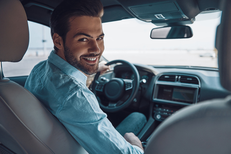 Are you ready to go? Rear view of young man in smart casual wear looking at camera over shoulder and smiling while driving a status car Stock Photo