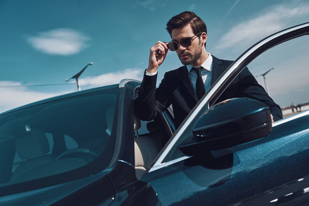 Luxury lifestyles. Handsome young man in business wear adjusting his sunglasses while standing near his car Фото со стока