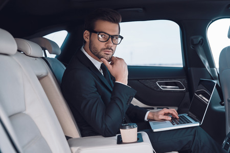 Successful professional. Thoughtful young man in full suit working using laptop and adjusting his eyewear while sitting in the car