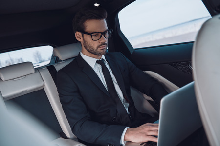 Young and successful. Handsome young man in full suit working using laptop while sitting in the car
