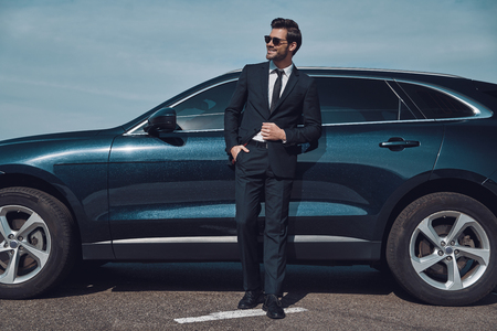 Great sense of style. Full length of handsome young businessman smiling while standing near his car outdoors