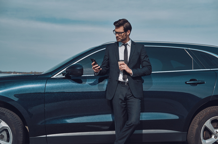 Typing business message. Handsome young businessman using smart phone and drinking coffee while standing near his car outdoors 免版税图像