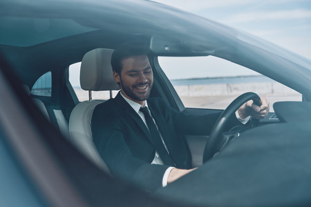 So happy! Handsome young man in full suit smiling while driving a car Banco de Imagens
