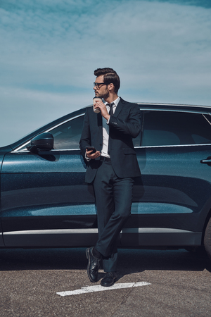 Time for a little break. Full length of handsome young businessman using smart phone and drinking coffee while standing near his car outdoors