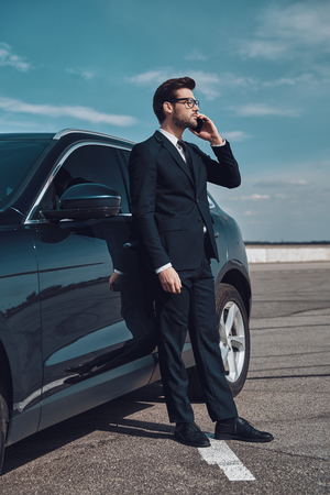 Talking about business. Full length of handsome young businessman talking on the phone while standing near his car outdoors