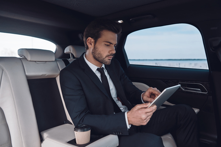 Considering the next step. Handsome young man in full suit working using digital tablet while sitting in the car