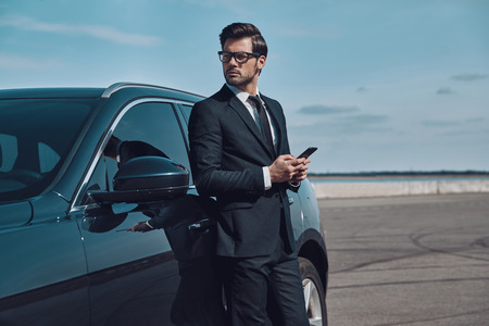 Business is his life. Handsome young businessman using smart phone while standing near his car outdoors Stok Fotoğraf