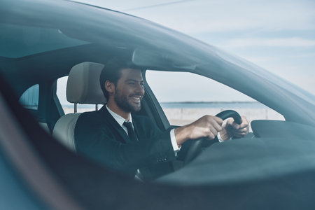 Feeling the road. Handsome young man in full suit smiling while driving a car