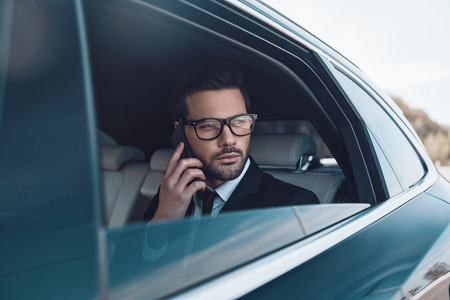 Discussing business details. Thoughtful young businessman talking on the phone while sitting in the car