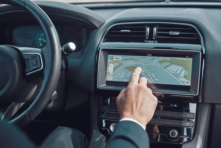 Planning the best route. Close up of man using global positioning system device to check the map while driving a car Stockfoto