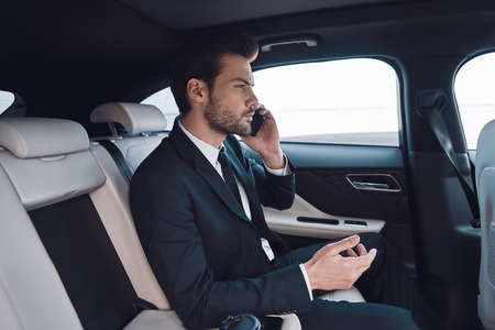 Always available. Handsome young man in full suit talking on the smart phone while sitting in the car