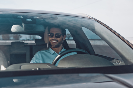 Convenience way to travel. Handsome young man smiling while driving a status car Banco de Imagens - 122384239