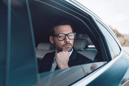 Thinking about business. Thoughtful young businessman keeping hand on chin while sitting in the car Banco de Imagens
