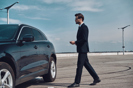 Modern businessman. Full length of handsome young businessman walking to his car Stok Fotoğraf