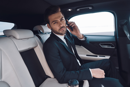 Busy day. Handsome young man in full suit talking on the smart phone and looking at camera while sitting in the car Stok Fotoğraf - 122384246