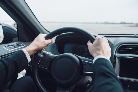 Drive carefully! Close up of man keeping hands on the steering wheel while driving a car