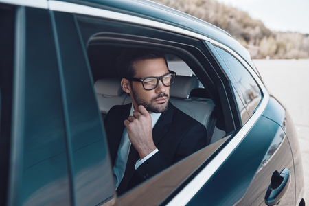 Thinking about... Thoughtful young businessman keeping hand on chin while sitting in the car Banco de Imagens - 122384271