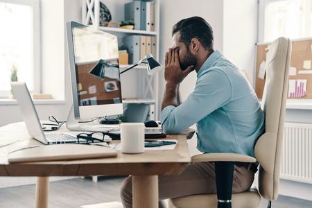 Erschöpfung. Müder junger Mann in eleganter Freizeitkleidung, der das Gesicht in den Händen hält, während er im Büro sitzt