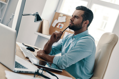Focusing on work. Young modern businessman thinking about something while sitting in the office