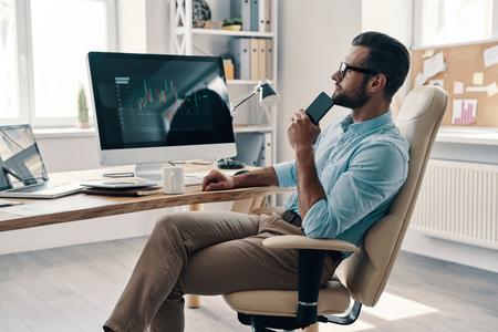 Desarrollar nuevos enfoques. Joven empresario moderno con teléfono inteligente y sonriendo mientras está sentado en la oficina