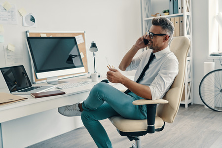 Successful professional. Good looking young man in shirt and tie talking on the smart phone and smiling while sitting in the office