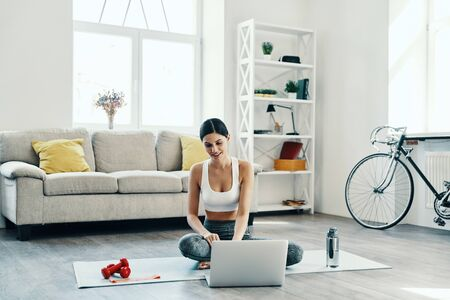 Looking for fresh sport videos. Beautiful young woman in sports clothing using laptop and smiling while exercising at home
