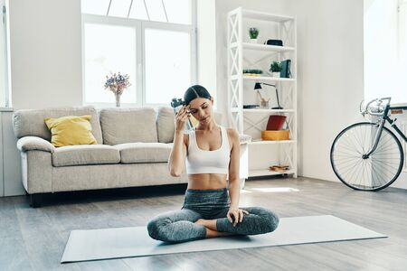 Just a minute to rest. Beautiful young woman in sports clothing practicing yoga and drinking yoga while spending time at home