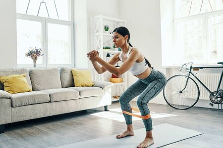 Achieving best results. Beautiful young woman in sports clothing crouching while exercising at home