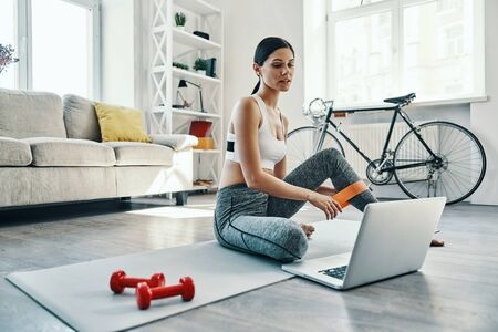 Haciendo todo bien. Hermosa mujer joven en ropa deportiva usando laptop mientras hace ejercicio en casa