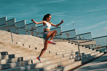 Always in a great shape. Full length of beautiful young woman in sports clothing running while exercising outdoors