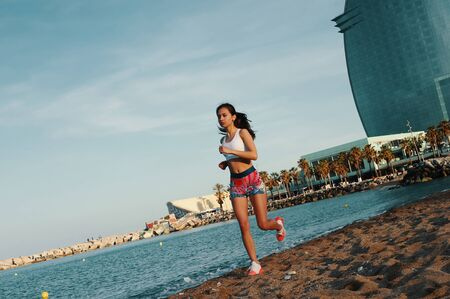 Filled with energy. Full length of attractive young woman in sports clothing jogging while exercising outdoors