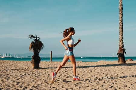 Always in shape. Full length of beautiful young woman in sports clothing jogging while exercising outdoors