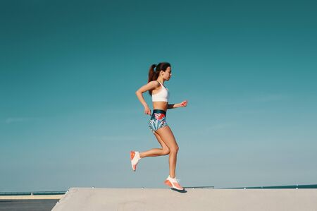 Sport is the way of her life. Full length of beautiful young woman in sports clothing jogging while exercising outdoors