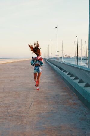 Making effort. Full length rear view of beautiful young woman in sports clothing running while exercising outdoors