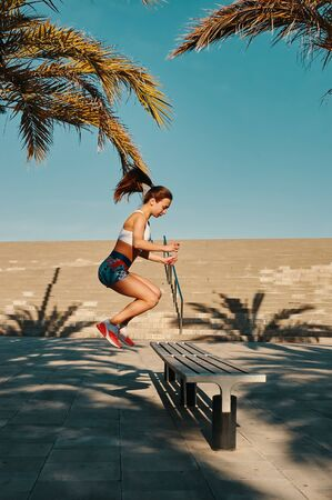 Challenging herself. Full length of beautiful young woman in sports clothing jumping while exercising outdoors Stock fotó