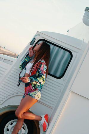 Jung und unbeschwert. Attraktive junge Frau, die in den Spiegel schaut und ihre Lippen anpasst, während sie draußen gegen einen Imbisswagen steht