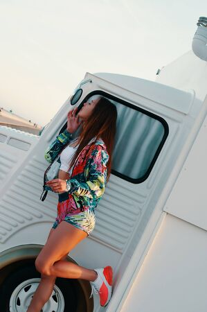 Young and carefree. Attractive young woman looking in the mirror and adjusting her lips while standing against food truck outdoors Stockfoto