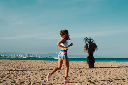 Nice day for jogging. Full length of beautiful young woman in sports clothing jogging while exercising outdoors Banco de Imagens - 126412810