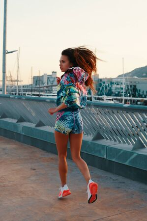 Keep moving! Full length of beautiful young woman in sports clothing running while exercising outdoors