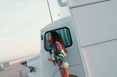 Everything should be perfect. Attractive young woman looking in the mirror while standing against food truck outdoors Stockfoto