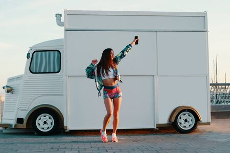 Just love your life! Full length of attractive young woman in sports clothing dancing while standing against food truck outdoors