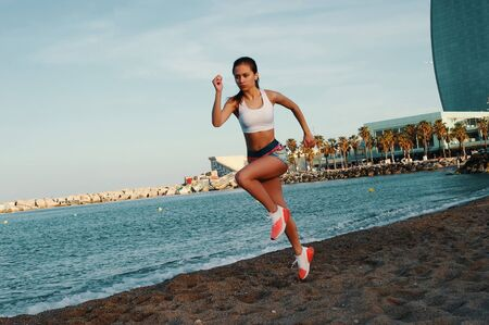 Fitness is the way of life. Attractive young woman in sports clothing jogging while exercising outdoors