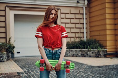 So cute! Beautiful young woman looking at camera and carrying skateboard while standing outdoors
