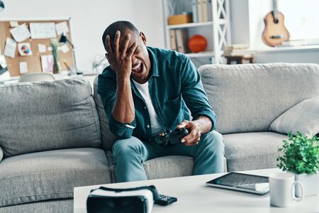 Oh no! Disappointed young African man covering face with hand while sitting on the sofa at home Stok Fotoğraf